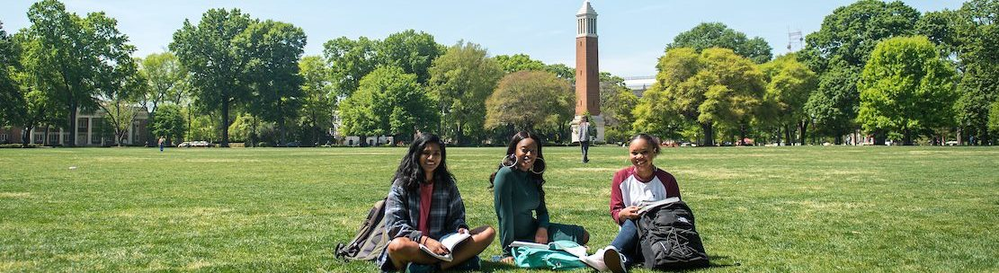 three students sitting in front of denny chimes